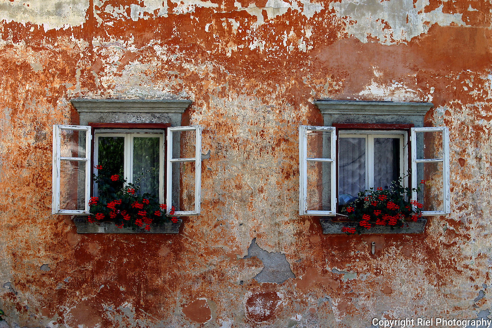 The patina on this red wall is great match for these window's flower boxes.