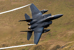 United States Air Force McDonnell-Douglas F-15E Strike Eagle (LN 91-335) from the 48th Fighter Wing, 494th Fighter Squadron based at RAF Lakenheath, England, flies low level through the Mach Loop, Machynlleth, Wales, United Kingdom
