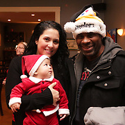 Josephine Miller, left, Tony Miller, 6 months, center, and Tony Miller pose for a picture Sunday December 21, 2014 during the Brooklyn Arts District Christmas party at Canape in Wilmington, N.C. (Jason A. Frizzelle)