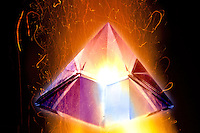 burning crystal pyramid  in fire flame in red,white and yellow color on black background