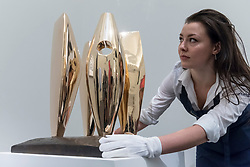 "© Licensed to London News Pictures. 16/11/2018. LONDON, UK. A technician presents ""Four Figures Waiting"", 1968, by Dame Barbara Hepworth (Est. GBP350,000-450,000). Preview of Sotheby's autumn sale of Modern & Post War British art.  Works from the British art scene of the past century will be offered for sale on 20 and 21 November 2018 at Sotheby's in London.  Photo credit: Stephen Chung/LNP"
