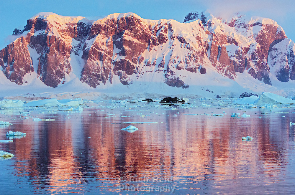 Sunset mountain refelction of the Graham Coast from the Grandidier Channel in Antarctica.