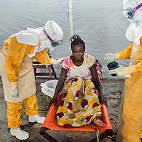 19/04/2014. Quartier de Kango II. Gueckedou. Guin&eacute;e Conakry.  <br /> <br /> Suite &agrave; un appel, une &eacute;quipe de MSF va chez Finda Marie Kamano, 33 ans, elle ressent une grande faiblesse, avec des vomissements et dysenterie. Avec la fi&egrave;vre, et les saignements de nez, ce sont les sympt&ocirc;mes provoqu&eacute;s par le virus Ebola.<br /> <br /> Apr&egrave;s lui avoir donn&eacute; un peu d'eau &agrave; boire, la femme-m&eacute;decin doit lui annoncer que son test &agrave; l'Ebola est positif, Finda reste impassible, plusieurs membres de sa famille en sont d&eacute;j&agrave; morts ces derni&egrave;res semaines.<br /> <br /> Following a call, an MSF team goes to consult Finda Marie Kamano, 33 years, she feels great weakness with vomiting and dysentery. With fever, and nose bleeds, what the symptoms are caused by the Ebola virus.<br /> <br /> After giving her a little water to drink, the woman doctor must tell her that her test is positive to Ebola, Finda remains impassive, several members of his family have died during the last weeks.<br /> <br /> &copy;Sylvain Cherkaoui/Cosmos/MSF