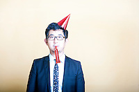 Asian business man wearing party hat