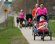 Led by Marie Boudreau-Ninkov pushing Nikki Knapik-Clauser, 17, of Chili, members of Ainsley's Angels run along Ayrault Road in Fairport on Sunday, April 26, 2015.