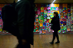 Commuters walk past thousands of pictures of flowers drawn by students from local schools are on display at the walls of Jefferson Station, in Center City Philadelphia, PA, on March 11, 2019.