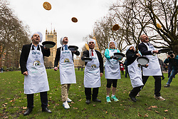 MPs and members of the House of Lords compete in the annual Rehab pancake race, a relay of eleven laps in Victoria Tower Gardens adjacent to the Houses of Parliament in London. The race is held every year on Shrove Tuesday and was won by the Media team. PICTURED: The Parliamentary team do a practice flip.  London, February 13 2018.