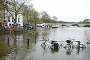 © Licensed to London News Pictures. 30/03/2014. Richmond, UK. Bikes caught up in the high tide chained to a fence post.  The high tide on the River Thames causing flooding in Richmond this afternoon 30th March 2014. Photo credit : Stephen Simpson/LNP