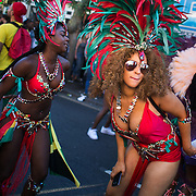 Young women in red show of their costumes and moves in the procession moving up the high street  in East London, United Kingdom,Sept 11 2016. The annual Hackney Carnival took place on a hot summers day and the procession of dancers dressed in various outfits moved through the streets to much joy of the many bystanders.