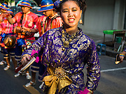 30 OCTOBER 2014 - BANGKOK, THAILAND: Traditional Thai dancers perform on Boriphat Street during the parade marking the start of the annual temple fair at Wat Saket. Wat Saket is on a man-made hill in the historic section of Bangkok. The temple has golden spire that is 260 feet high which was the highest point in Bangkok for more than 100 years. The temple construction began in the 1800s in the reign of King Rama III and was completed in the reign of King Rama IV. The annual temple fair is held on the 12th lunar month, for nine days around the November full moon. During the fair a red cloth (reminiscent of a monk's robe) is placed around the Golden Mount while the temple grounds hosts Thai traditional theatre, food stalls and traditional shows.   PHOTO BY JACK KURTZ