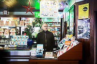 "NAPLES, ITALY - 12 DECEMBER 2014: Pino De Stasio, owner of cafè Bar Settebello, is here behind the cash register in his cafè in Naples, Italy, on December 12th 2014. Bar Settebello is part of the ""Rete del Caffè Sospeso"" (Suspended Coffee Network).<br /> <br /> A caffè sospeso,or suspended coffee, is a cup of coffee paid for in advance as an anonymous act of charity. The tradition began in the working-class cafés of Naples, where someone would order a sospeso, paying the price of two coffees but receiving and consuming only one. A poor person enquiring later whether there was a sospeso available would then be served a coffee for free."