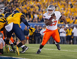 Oct 10, 2015; Morgantown, WV, USA; Oklahoma State Cowboys running back Rennie Childs runs the ball for a touchdown during the second quarter against the West Virginia Mountaineers at Milan Puskar Stadium. Mandatory Credit: Ben Queen-USA TODAY Sports