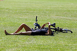 © Licensed to London News Pictures. 20/05/2020. London, UK. A woman takes a break from cycling and relaxes in Markfield Park, Tottenham, north London on a warm and sunny day in London. The government has relaxed the rules on the COVID-19 lockdown, allowing people to spend more time outdoors whilst following social distancing guidelines. According to the Met Office, 27 degrees celsius is forecast for today.  Photo credit: Dinendra Haria/LNP