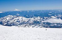 A man glisading / sliding down the Muir Snow Field on Mt. Rainier's south side with the Tatoosh Range seen down below in the background.
