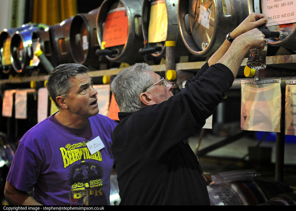© Licensed to London News Pictures. 07/03/2012. London, UK. A volunteer pours a pint of ale from the temporary racks of kegs installed for the festival. The Campaign for Real Ales' (CAMRA) London Drinker Beer & Cider Festival at the Camden Centre, London today 07 March 2012. Over 70 real ales, ciders and perries from over 50 breweries are available alongside imported beers. The festival runs Wednesday 07 March 2012 - Saturday 10 March 2012. Photo credit : Stephen SImpson/LNP