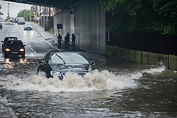 © Licensed to London News Pictures. 23/06/2016. London, UK. As rainwater collects under the railway bridge on the Rickmansworth Road, some drivers risk flooding their engines as they try to pass through after a torrential rain shower lasting for more than 30 minutes causes localised flooding in Northwood, north west London. Photo credit : Stephen Chung/LNP