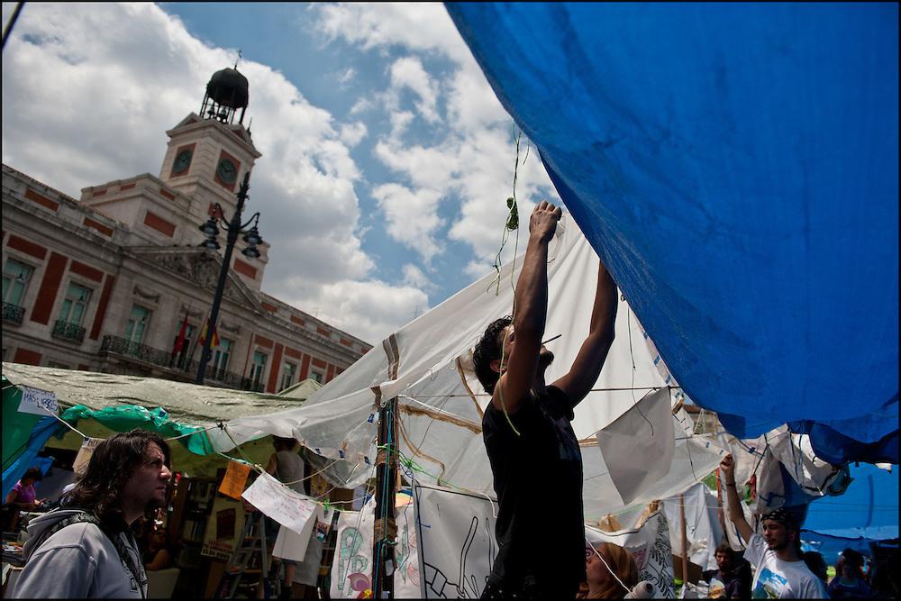 """Des baches sont utilisees pour proteger le campement. // Le mouvement spontane du """"15 M"""" (15 mai) compose de citoyens espagnols campe depuis 2 semaines sur la place Puerta Del Sol avec pour revendication la construction d'une democratie nouvelle. Organise en commission les citoyens prennent la parole lors d'assemblee ouverte a tous - Place Puerta Del Sol à Madrid le Juin 2011. ©Benjamin Girette/IP3Press"""