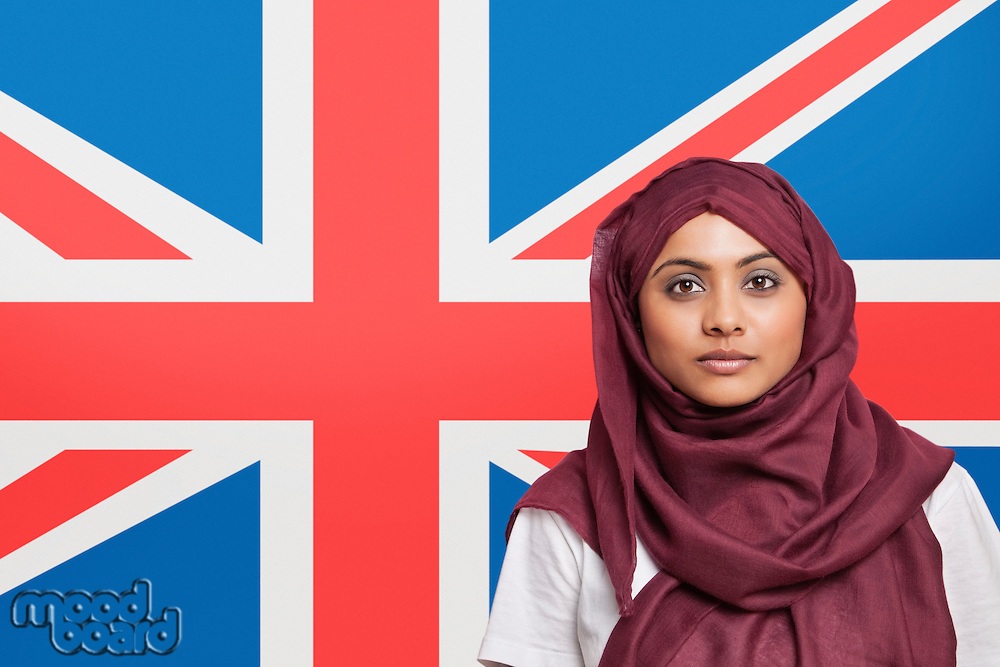 Portrait of young Muslim woman in traditional clothing standing against British flag
