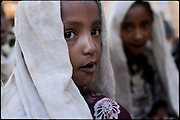"Ishalem, 6 yeras old, eats some food, after a long night spent awake during her marriage's celebration. The festivities will extend over several days, the only way to encourage young brides is to allow them to drink tella, a local wine. Child marriage was a major issue raised by the 2007 United Nations Commission on the Status of Women. A U.S. resolution to reduce the practice was passed, encouraging countries to take actions. In Ethiopia the legal age to get married is 18, the law quite often is ignored. North West of Ethiopia, on saturday, Febrary 14 2009.....In a tangled mingling of tradition and culture, in the normal place of living, in a laid-back attitude. The background of Ethiopia's ""child brides"", a country which has the distinction of having highest percentage in the practice of early marriages despite having a law that establishes 18 years as minimum age to get married. Celebrations that last days, their minds clouded by girls cups of tella and the unknown for the future. White bridal veil frame their faces expressive of small defenseless creatures, who at the age ranging from three to twelve years shall be given to young brides men adults already...To protect the identities of the recorded subjects names and specific places are fictional."