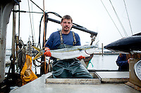 Doug McCall, fisherman, holds up a catch of tuna on the boat Intrepid at the Newport, Oregon harbor.