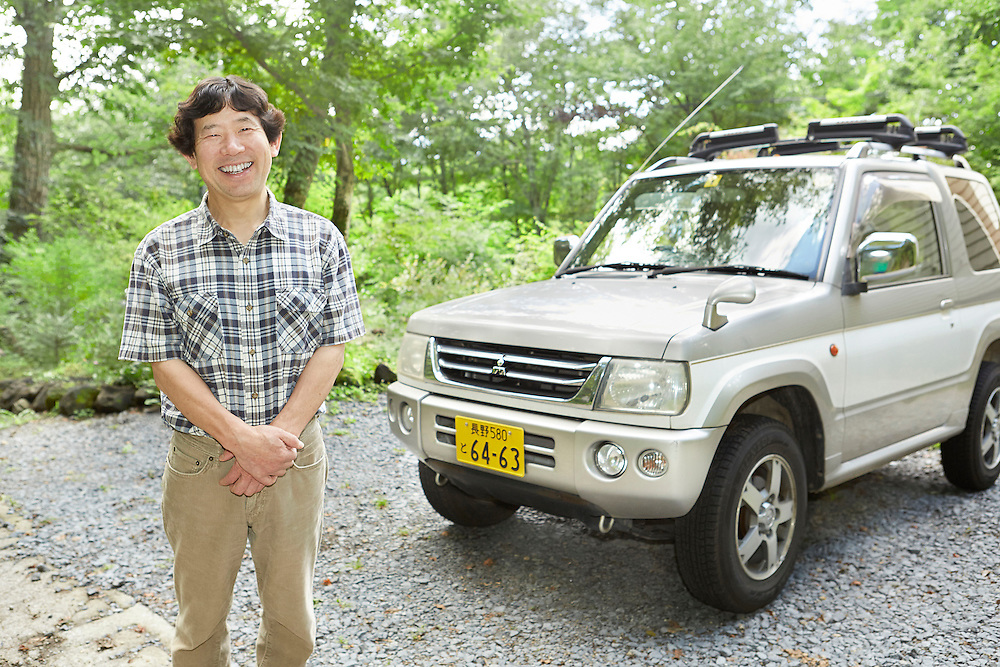 Lifestyle image of smiling middle age man standing in front of Mitsubishi 4WD SUV car