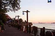 Sunset with blue lights and Statue of Liberty at Battery Park City, New York.