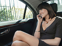 Mid adult woman at back seat of car using mobile phone