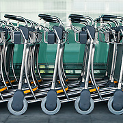 A row of empty luggage carts at an airport.<br />