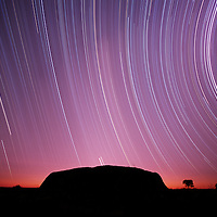 Australia, Northern Territory, Ulru - Kata Tjuta National Park, Star trails circle above Ayers Rock at night during eight hour time exposure