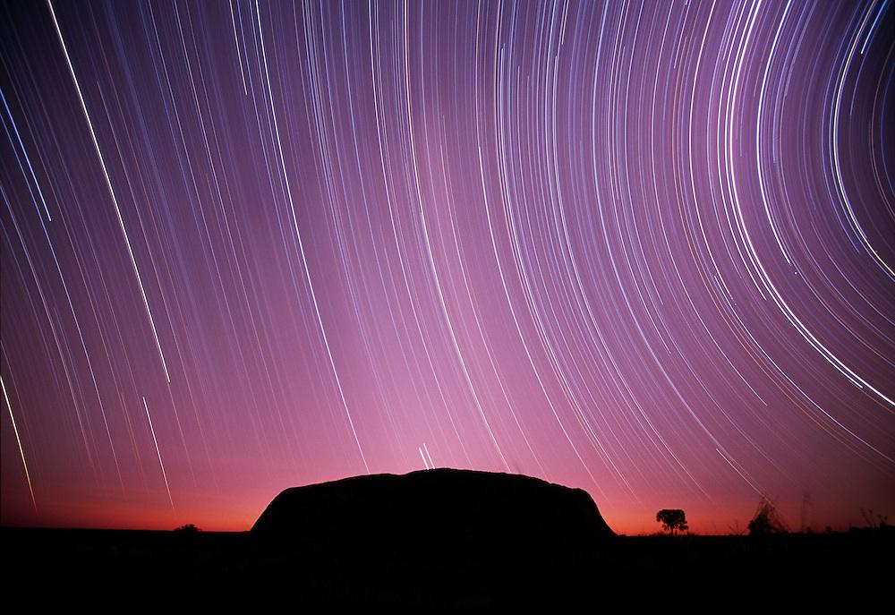 Australia, Northern Territory, Ulru - Kata Tjuta National Park, Star trails circle above Ayers Rock at night during eight hour time exposure