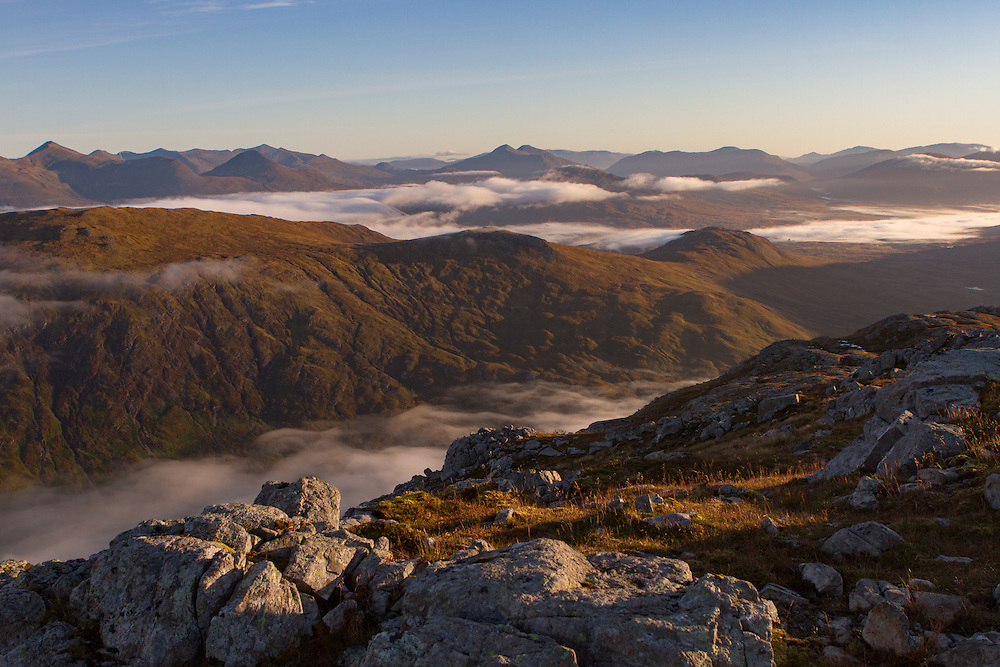 Morning light reaches over over the pass of Glencoe from Stob Coire Raineach.
