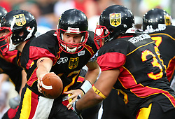 10.07.2011, Tivoli Stadion, Innsbruck, AUT, American Football WM 2011, Group A, Germany (GER) vs United States of America (USA), im Bild Joachim Ullrich (Germany, #12, QB) hands the ball over to Jerome Morris (Germany, #38, RB)  // during the American Football World Championship 2011 Group A game, Germany vs USA, at Tivoli Stadion, Innsbruck, 2011-07-10, EXPA Pictures © 2011, PhotoCredit: EXPA/ T. Haumer