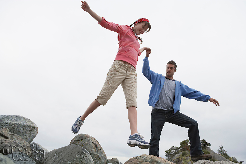 Couple holding hands jumping on rocks