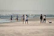 Youngsters play and walk their dogs on the stunning windswept West coast beach of Melkbosstrand, North of Cape Town, South Africa