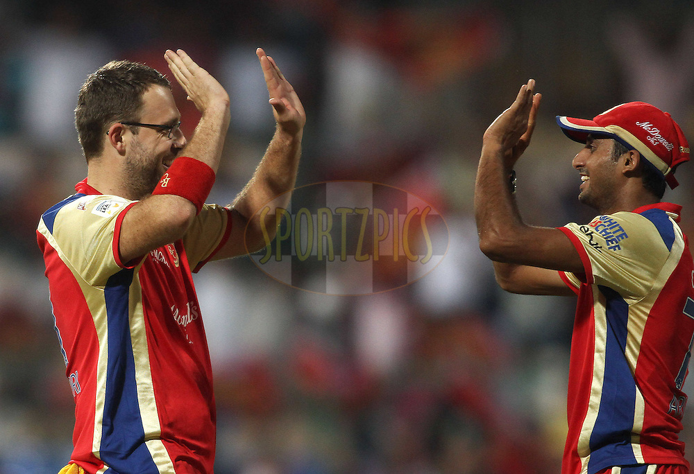 Daniel Vettori of Royal Challengers Bangalore celebrates with Sreenath Aravind of Royal Challengers Bangalore after getting Justin Kreusch of the Warriors wicket during match 1 of the NOKIA Champions League T20 ( CLT20 )between the Royal Challengers Bangalore and the Warriors held at the  M.Chinnaswamy Stadium in Bangalore , Karnataka, India on the 23rd September 2011..Photo by Shaun Roy/BCCI/SPORTZPICS