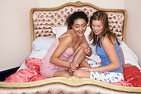 Teenage girl painting friend's fingernails on bed at slumber party
