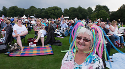 © Licensed to London News Pictures.22/08/15<br /> Castle Howard, North Yorkshire, UK. <br /> <br /> A woman with a colourful hat enjoys the music as hundreds of people attend the 25th anniversary of the Castle Howard Proms event near York. The theme of the event this year is a commemoration of the 75th anniversary of the Battle of Britain and the 70th anniversary of VE day and brings an evening of classic musical favourites celebrating Britishness to the lawns of Castle Howard.<br /> <br /> Photo credit : Ian Forsyth/LNP