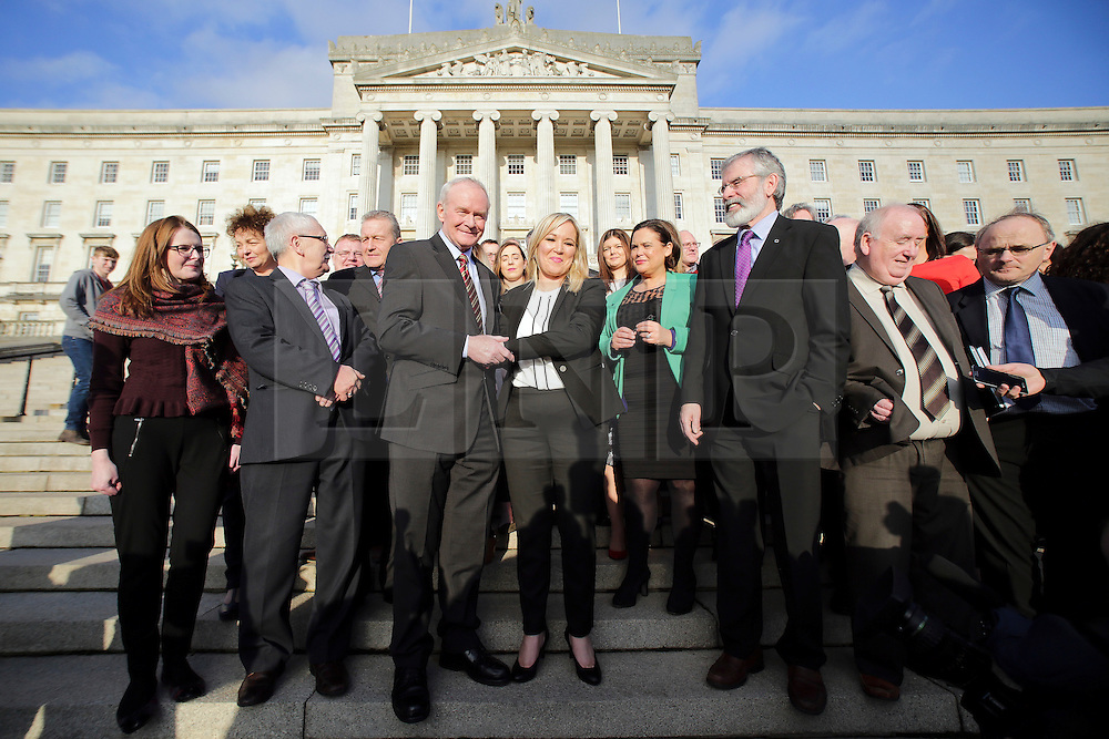 © Licensed to London News Pictures. STORMONT BELFAST - 23 JAN 2017: Sinn Fein's Michelle O'Neill (centre) shakes hands with Martin McGuinness, while stood next to Gerry Adams (third from right), on the steps of Stormont after being named as the new leader of Sinn Fein in the North, taking over from former deputy first minister Martin McGuinness who has retired due to illness. Photo credit: London News Pictures.