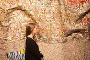 "UNITED KINGDOM, London: 1 February 2016 A Bonham's staff member takes a close look at El Anatsui's ""Peju's Robe"" (estimated to be worth £450,000 - 550,000) made from thousands of pressed bottle tops which forms part of the Post-War Contemporary Art Sale which opens 11th of February 2016. Other work includes Andy Warhol's ""Fourteen Small Electric Chairs"" estimated to be worth £4,000,000 - 6,000,000. Rick Findler  / Story Picture Agency"