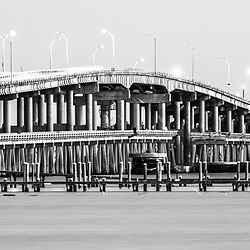 Bob Sikes Bridge and Grand Marlin restaurant Pensacola Beach Florida black and white panoramic photo. The Bob Sikes Bridge connects Gulf Brezze Florida with Pensacola Beach on Santa Rosa Island. Panorama photo ratio is 1:3. Copyright ⓒ 2018 Paul Velgos with All Rights Reserved.