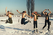 Four Teenagers jump topless in a snowy day at London park. London, Greenford, UK, 1981.