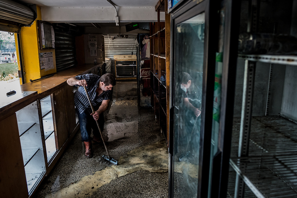 CARACAS, VENEZUELA - APRIL 21, 2017:  Victor Orlando Gómez, 50, cleans debris from inside Tintalim supermarket, that was one of over a dozen stores looted late last night in El Valle, a working class neighborhood in Caracas. The streets of Caracas erupted into a night of riots, looting and clashes with National Guardsmen as anger from two days of pro-democracy protests spilled into unrest in working class neighborhoods and slums. Shots rang out throughout the night in El Valle, a neighborhood of mixed loyalties, as armored vehicles struggled to contain crowds of looters. At one point during the night, clashes became so heavy that a nearby children's hospital was evacuated after the ward filled with tear gas. The government said they were responding to an attack on the hospital by opposition protestors.  PHOTO: Meridith Kohut