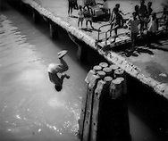 Coin diver from nearby slums flips into Cebu Bay where he will dive for coins thrown down from passenger ferry to outer island, Philippines.  The boys help supplement their parents' inadequate income.