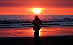 © Licensed to London News Pictures. <br /> 17/04/2015. <br /> <br /> Saltburn, United Kingdom<br /> <br /> A woman crouches to take a photo of a spectacular sunrise at Saltburn in Cleveland.<br /> <br /> Photo credit : Ian Forsyth/LNP