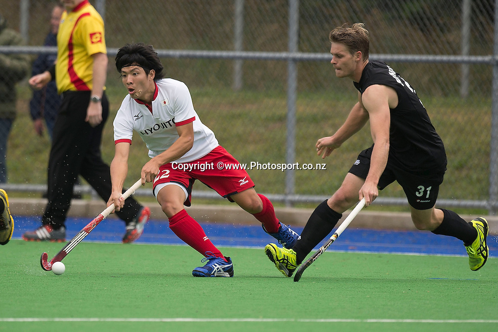 Shunya Miyazaki (L) of Japan looks to pass under pressure by Steve Edwards of New Zealand during the Black Sticks Men v Japan international hockey match at the Coastlands Kapiti Sports Turf in Paraparaumu on Friday the 22nd of November 2014. Photo by Marty Melville/www.Photosport.co.nz