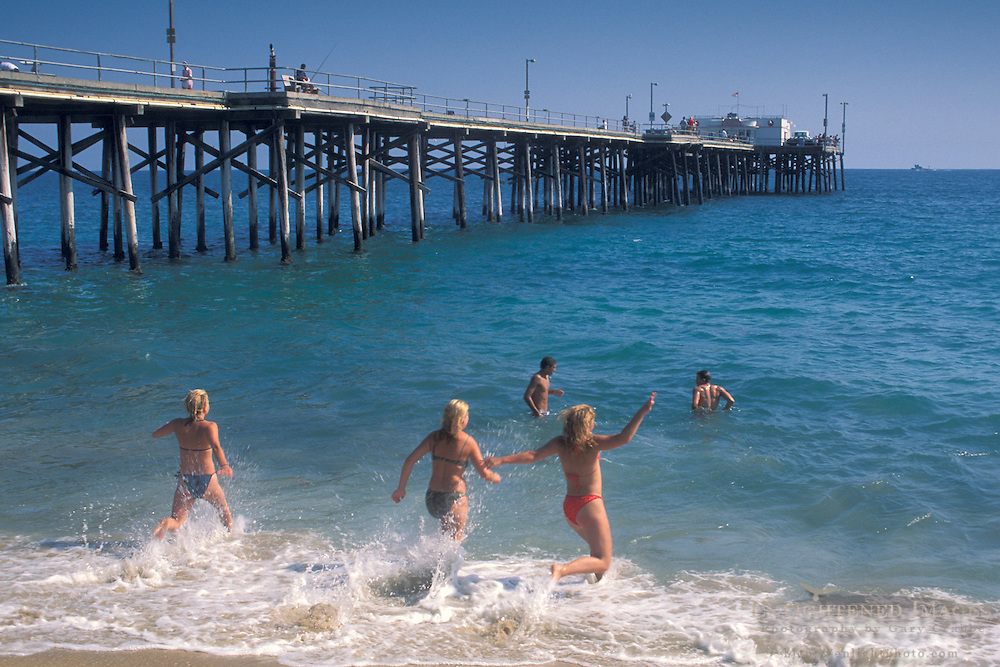 Young girls run into ocean water from sand beach at Balboa Pier, Balboa Island, Newport Beach, California