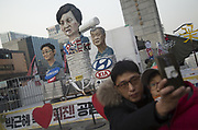 A South Korean man and his son take pictures of them in front of a work that local artists created to criticize South Korean President Park Geun-hye (C), Samsung Electronics Vice Chairman Lee Jae-Yong (L) and Hyundai Motor Chairman Chung Mong-Koo during a rally in Seoul, South Korea, Jan 7, 2017. About 600,000 people on Saturday participated in a rally in Seoul, held over an influence-peddling scandal centered on Park and her long-time friend Choi Soon-Sil. Park and Choi allegedly extracted US$64.7 million from conglomerates to set up private foundations controlled by Choi. People demanded President Park to step down during a rally, which was held also to mourn over the 1,000th day of the Sewol Ferry disaster on April 16, 2014, which falls on January 9, 2016. Photo by Lee Jae-Won (SOUTH KOREA) www.leejaewonpix.com