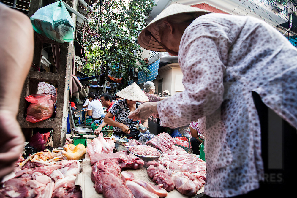 An elderly Vietnamese woman leans over a meat stand at a local market in Hanoi, Vietnam, Southeast Asia