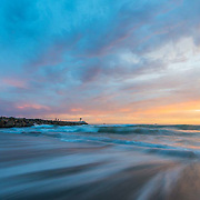 Waves crash and the sun sets over Monterey Bay from Moss Landing, California.