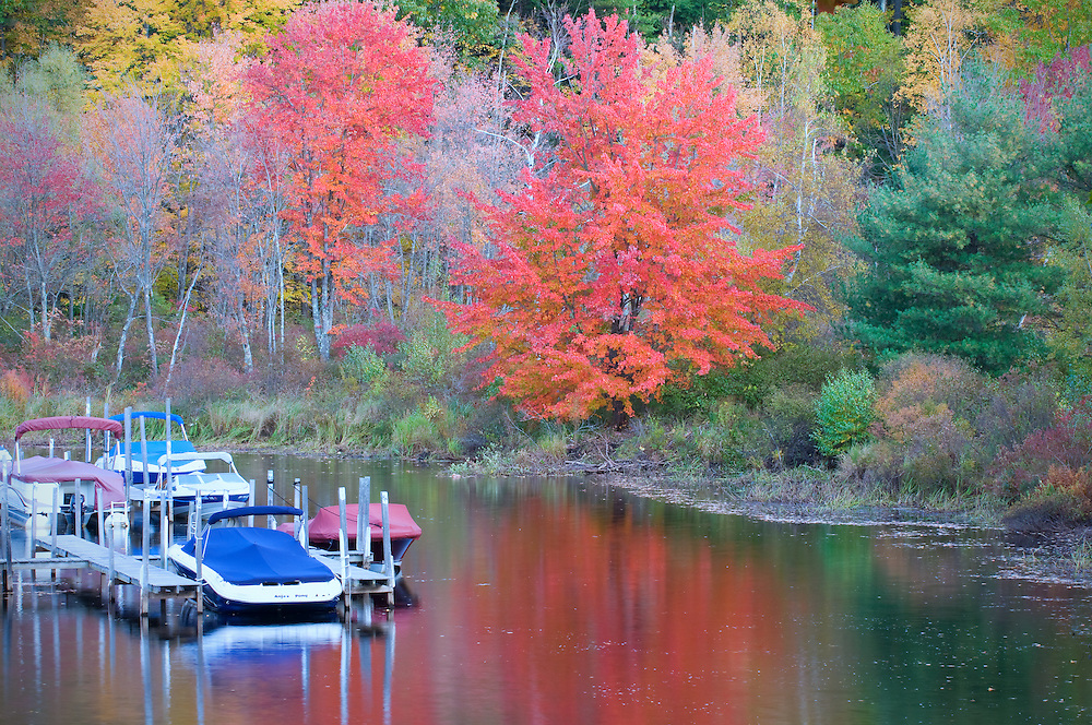 Docked boats in Autumn on a river in New Hampshire.